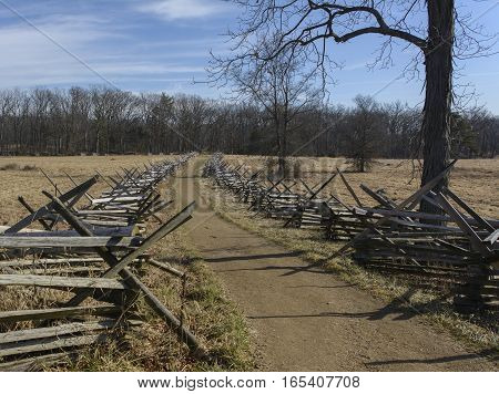 Two parallel split rail fences built in the iconic Gettysburg style separate 2 farm fields in Gettysburg Pennsylvania, USA.