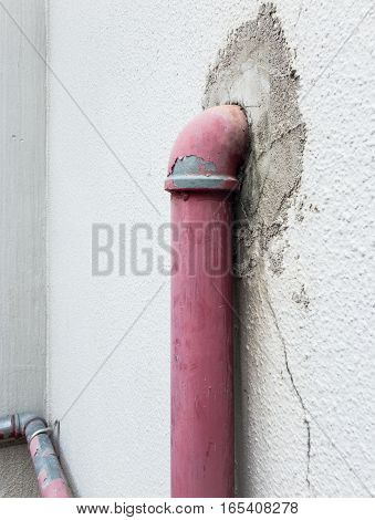 Old metal pipe for fire hydrant near the factory wall.
