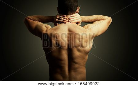 Cervical neck pain. Man back. Medical care. Adult man torso with two hands up to pain in the neck area. Isolated on neutral background with vignetting. Medical care.