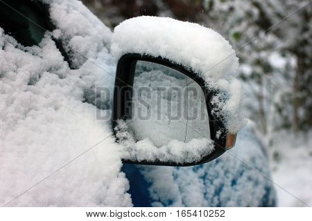 rear view mirror of car covered in snow
