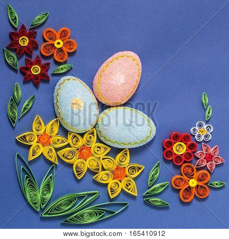 Colorful Easter composition with eggs and flowers in the technique of quilling on a blue background. Homemade application on paper. DIY Easter concept. Top view square image