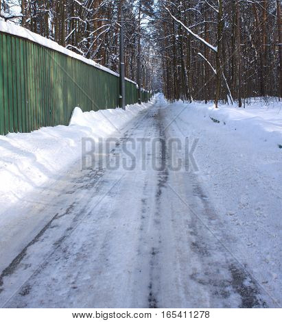 Landscape with Long straight winter road through forest along green high fence