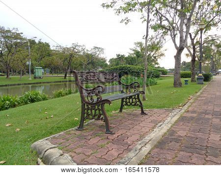 Dark colored wrought iron bench on the side of bricked walkway in public park