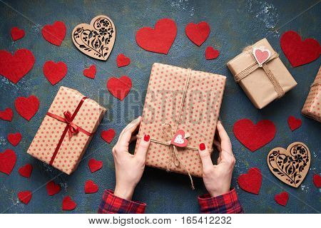 Close up on women's hands packing and presented a gift for valentine day, birthday, mother's or christmas. Flat lay. Top view table. Heart background on Valentines Day.
