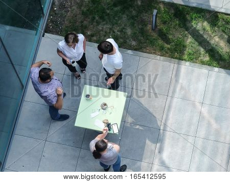 Bucharest Romania May 30 2016: People are smoking and drinking coffee in an outdoor smoking area of an office building in Bucharest.