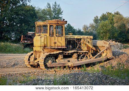 Yellow crawler tractor in gravel canyon. Crawler.
