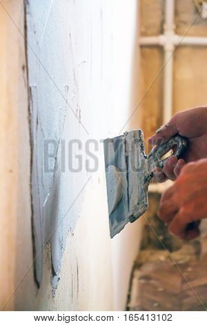 Man plastering wall in room with spatula 2