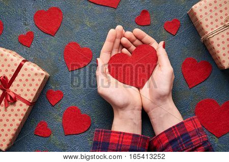 man hands holding Valentine heartsConcrete background with hearts and gifts on Valentine's Day. Symbol of love. The concept of a romantic Valentines Day. Flat lay. Top view table.