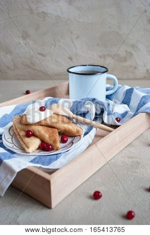 beautiful russian pancakes with sour cream, cranberry and vintage cup of tea on concrete background