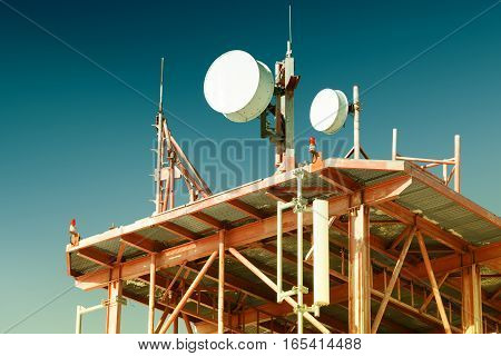 Telecommunications Tower With Many Antennas And Clear Blue Sky On Background. Filtered Image: Cross