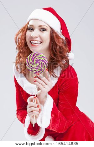 Portrait of Happy Smiling Santa Helper with Lollipop. Against white. Vertical Image Composition