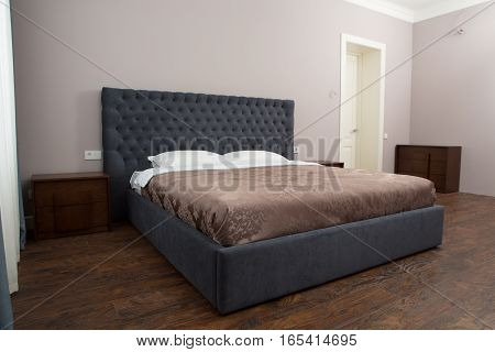 View of double bed in bedroom with two white pillows on. Representation of bed in hotel or luxurious house.
