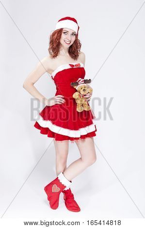Portrait of Caucasian Santa Helper with Miniature Present in Hands. Over White Background. Vertical Image