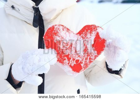 A girl holding a red heart on a snowy background.