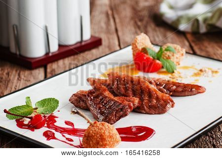 Grilled steaks with baked pear and sweet sauce. Restaurant serving of barbecue pork with berry topping. Gourmet food, luxury lifestyle, recipe, expensive concept