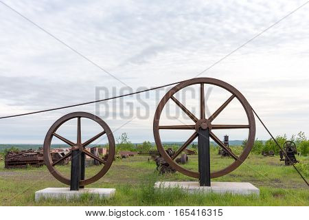 Large industrial wheels with a cable running over the top and various pieces of rusting equipment in the background. Concepts could include industry history decay or others. Copy space in sky if needed.