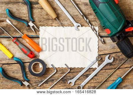 Electric and building tools on wooden background with paper card