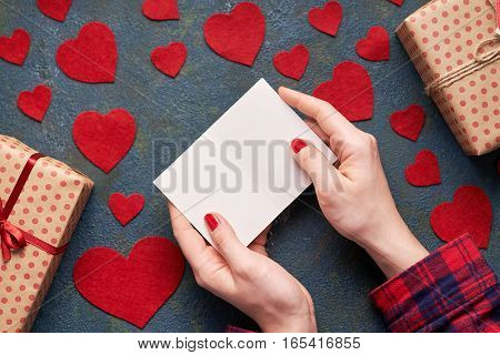 Woman's hands open Valentine card. Creative Background with hearts and gifts on Valentines Day. Flat lay. Top view table.