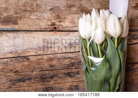 Tulips in bunch lying on the wooden background. Tulip flowers on wood