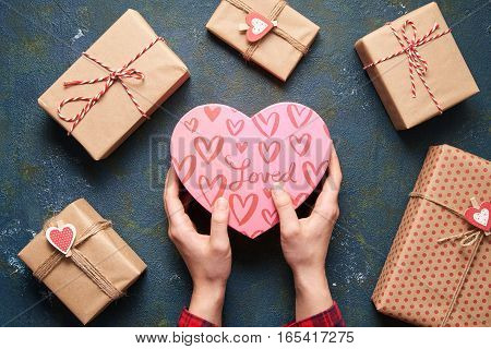 Close up on female hands holding a gift in a pink heart presents for valentine day, birthday, mother's day. Flat lay. Symbol of love. Valentines day background with a gift boxes on concrete board.
