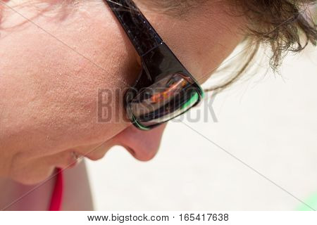 woman on the beach wearing sunglasses looking down on the sand