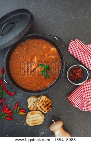Spicy fish stew with tomatoes in cast iron pot with grilled bread slices on rustic table, top view