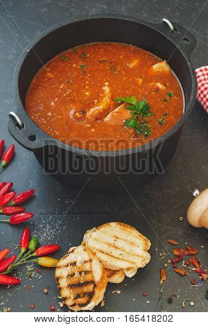 Mixed fish and tomato chowder  in cast iron pot with grilled bread slices on rustic table. Macro, selective focus