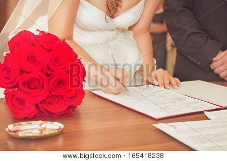 Elegant young couple standing at a reception desk with their passports with the beautiful woman smiling as she waits for service