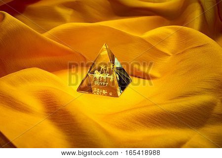 glass pyramid egypt souvenir on an orange background in the form of the desert with palm trees and camels