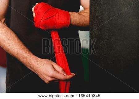 Male puts on red boxing bandages on his hands