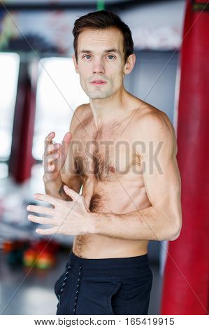 Portrait of young athlete without shirt in gym