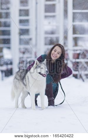 Portrait of Pretty Smiling Woman Hugging Her Husky Dog Outside. Vertical Image Composition