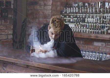 Young Man at vaping store is smoking