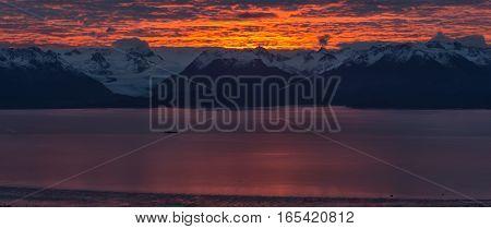 Kackemak Bay glows pink as the sun rises flinging golds and reds behind the Kenai Mountains.