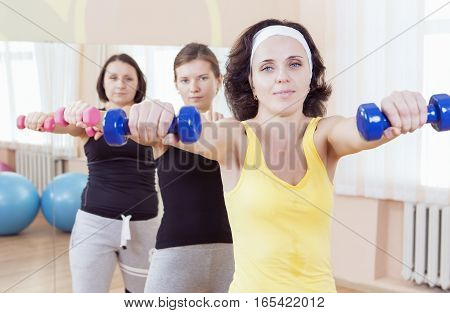 Sport and Fitness Ideas. Group of Three Caucasian Female Athletes Having a Workout Training with Barbells Indoors. Horizontal Shot