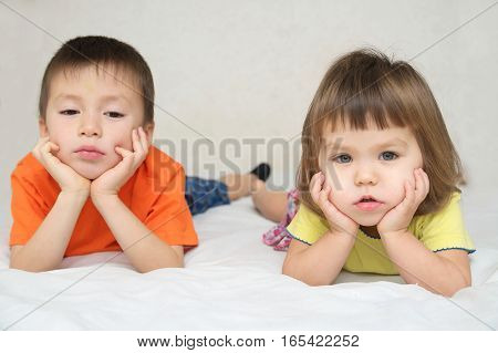 little boy and girl brother and sister quarreling on bed family relationships concept