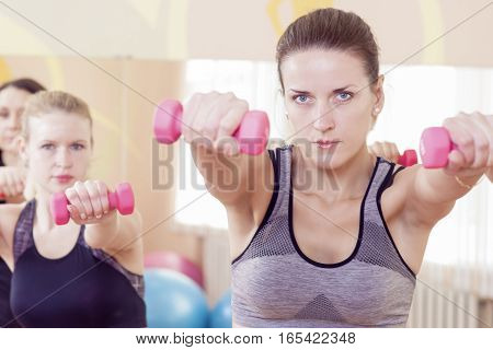 Three Caucaisan Fitness Girls Having a Workout With Barbells Indoors. Horizontal Image Orientation