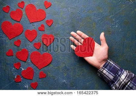 Red Heart Love is in Men's Hand. Concept for Valentine's day. Concrete background with hearts and gifts on Valentines Day. The concept of a romantic date. Flat lay. Top view table. Symbol of love.