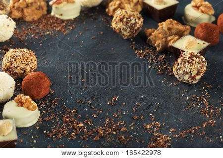 Different chocolate candy on a dark surface with copy space