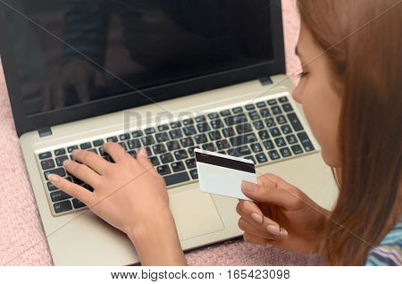 Closeup hand of girl typing credit card details on laptop to complete payment process. Close up of female hand paying bills online with laptop and credit card. Internet banking.