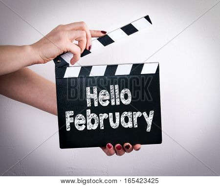 Hello February. Female hands holding movie clapper.