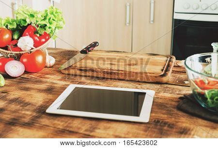 Ingredients for cooking healthy food on a wooden table with tablet in a home kitchen