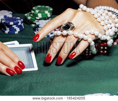 hands of young caucasian woman with red manicure at casino table close up