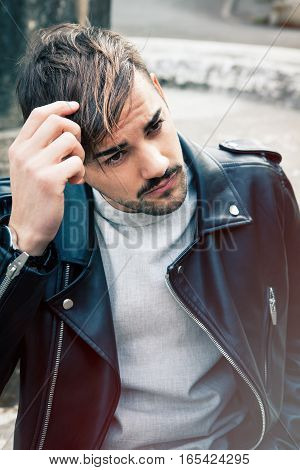 A young and handsome guy is outdoors touching the straight brown hair. Charming and youthful look. Leather jacket and light beard.