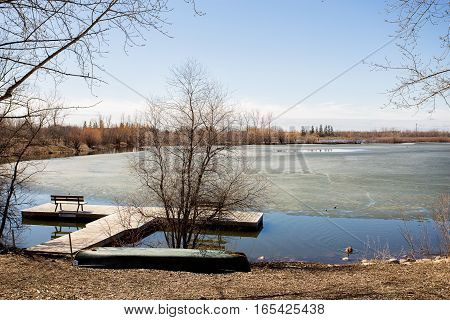Two canoes laying at a partially frozen rivers edge by floating wood dock in spring landscape