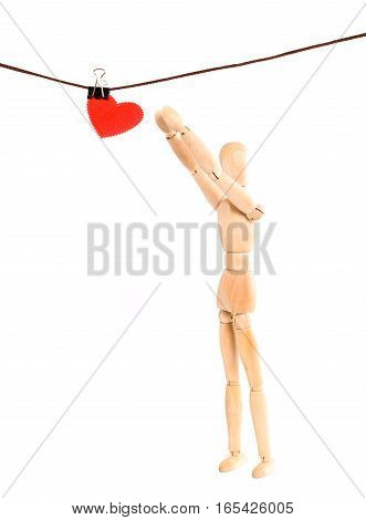 Wooden figure of the person and heart on a rope with a clothespeg. The person reaches hands for a red heart from fabric to hang up or remove him from a rope. It is isolated on a white background