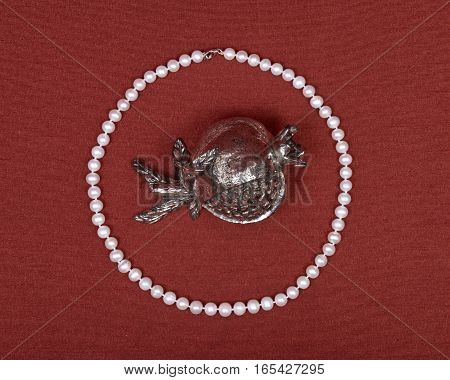 Freshwater white pearl necklace and pomegranate shabbat metal decoration on red fabric background
