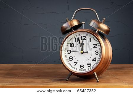 Retro the alarm clock of bronze color showing 12 hours on a table on a blue background.