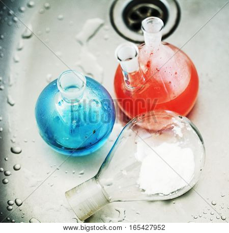 waste products in laboratory, medicine-glass with colored red and blue liquid close up