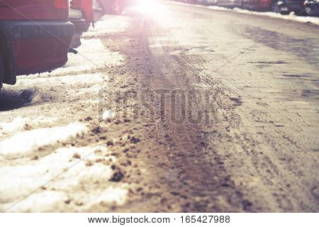 Tire Tracks In The Melting Snow On Asphalt Road, Vintage Effect And Flare
